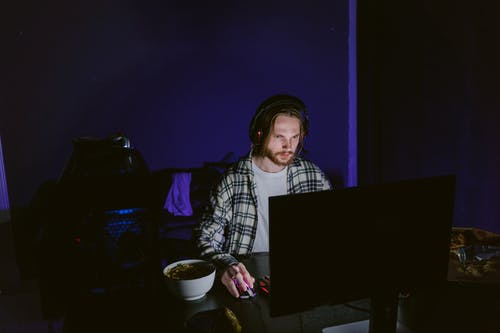 Man in Plaid Shirt Playing a Computer Video Game