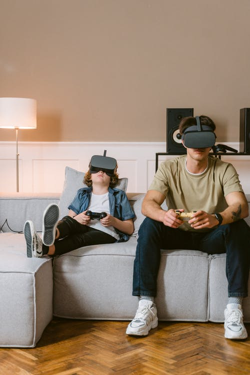 A Man and Boy Sitting on a Couch while Playing a Virtual Reality Video Game
