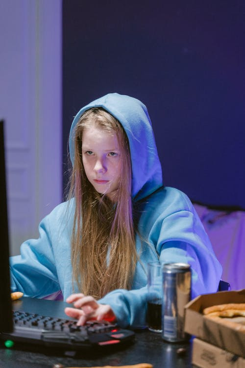 Woman in Blue Hoodie Sitting by the Table