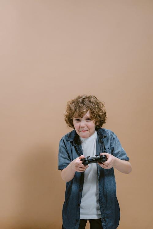 Smiling Boy in Blue Denim Jacket Holding Black Dslr Camera