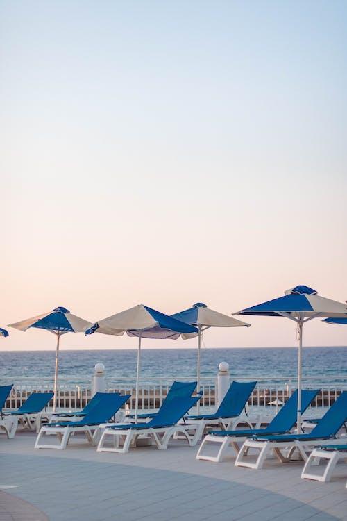 Sunbeds on sandy beach in summer