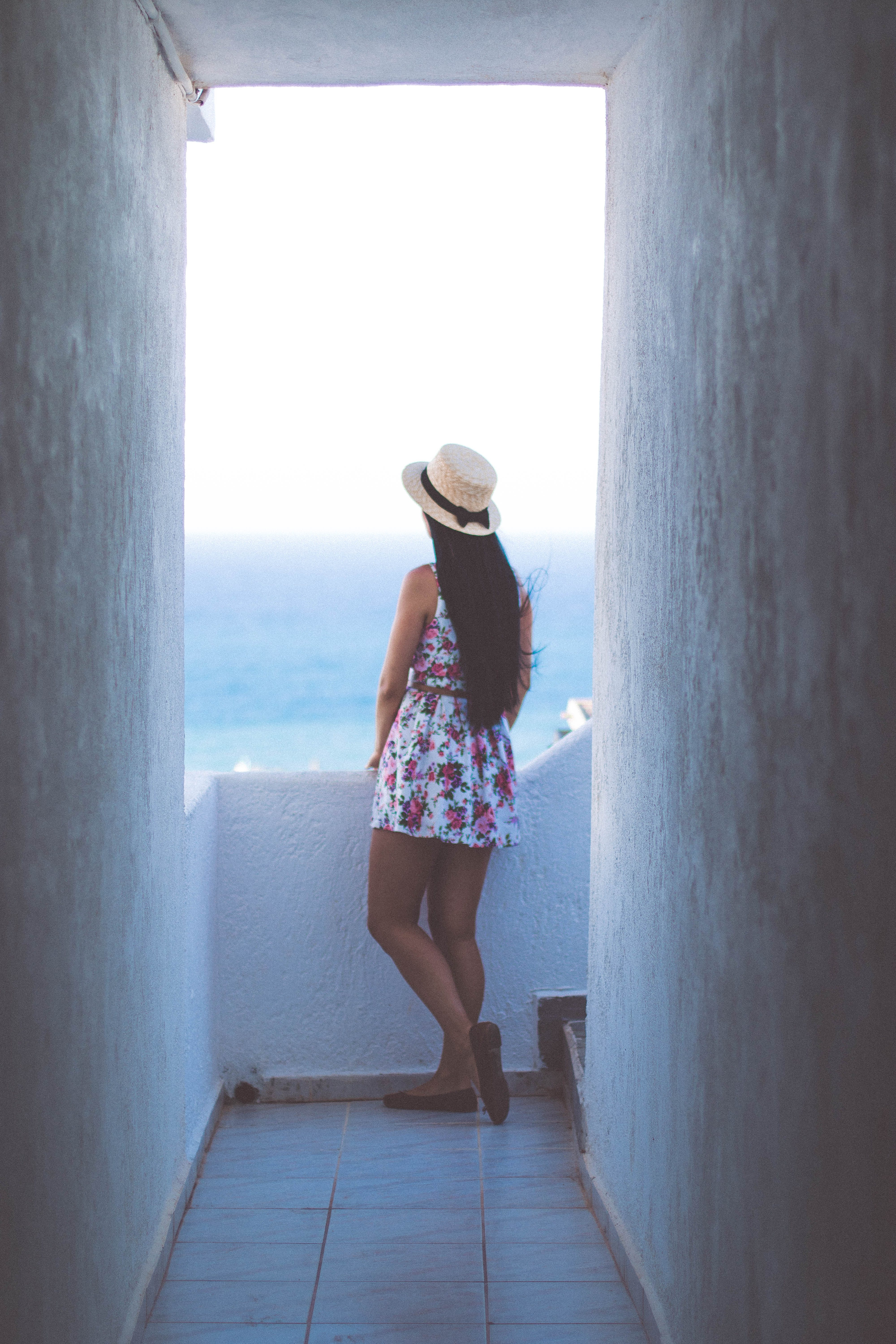 Woman in Pink Floral Midi Dress Standing on Balcony