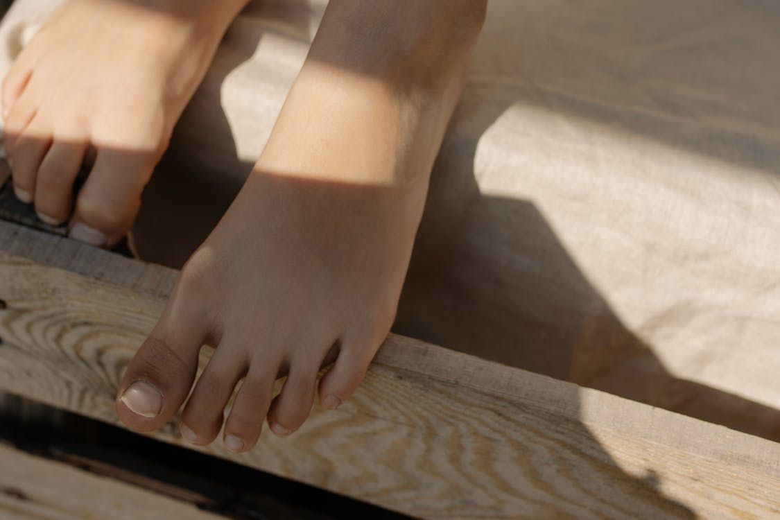 Persons Feet on Brown Wooden Table