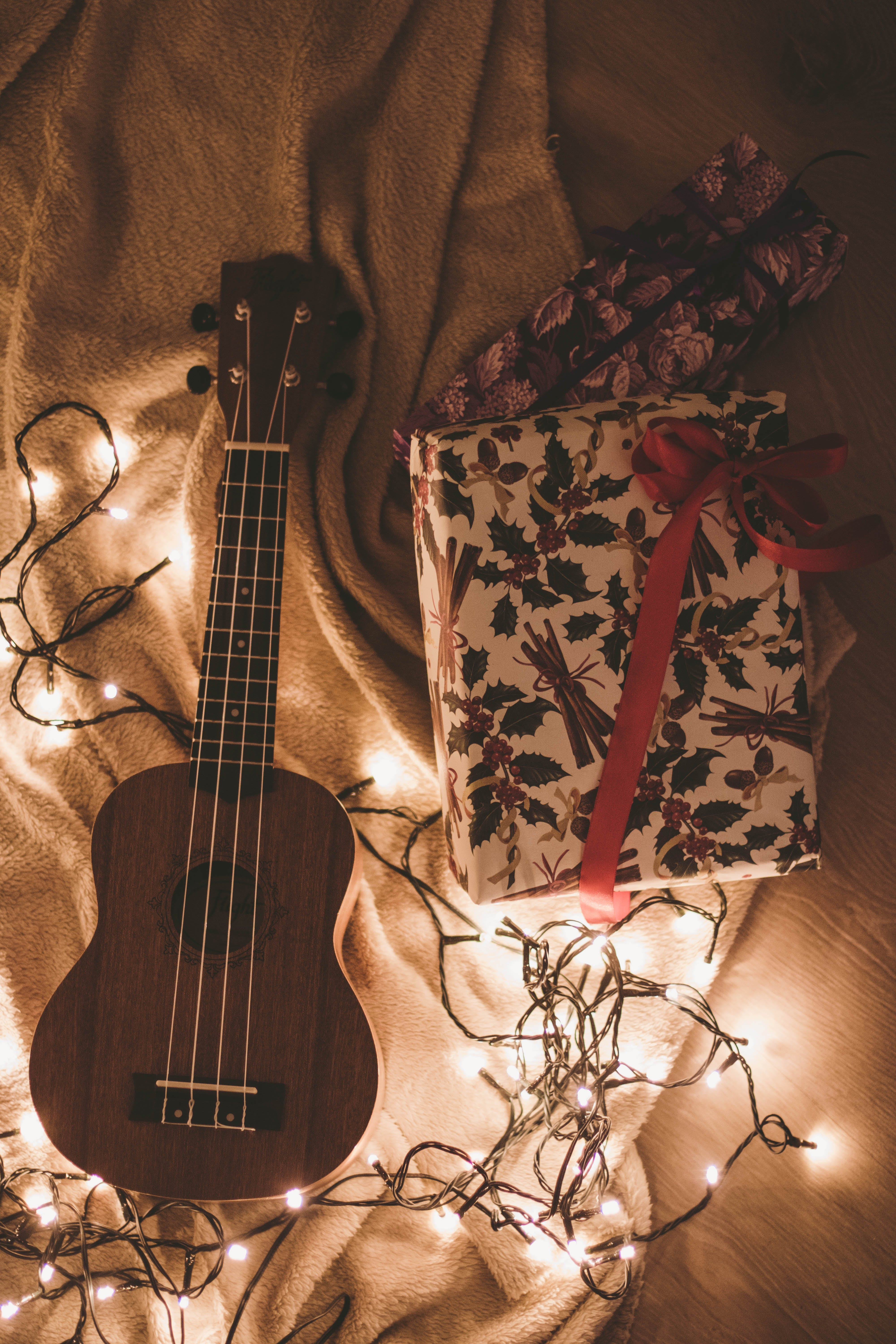Ukulele Beside a Floral Box and String Lights