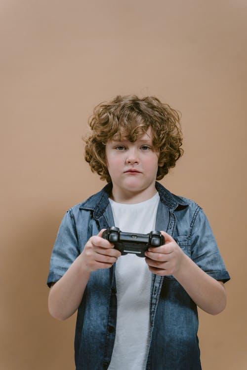 Boy in Blue Denim Button Up Jacket Holding Black Camera