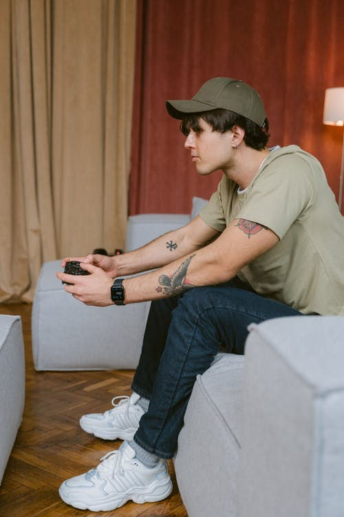 Man in Brown Button Up Shirt and Blue Denim Jeans Sitting on White Couch