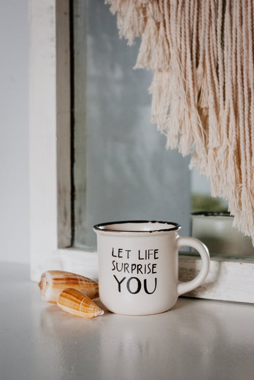 Mug with phrase placed near seashells on windowsill