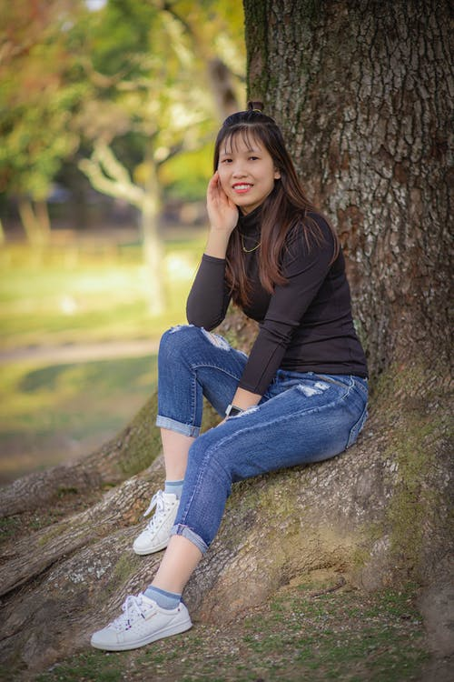A Woman in Black Long Sleeves Looking at Camera while Sitting under the Tree