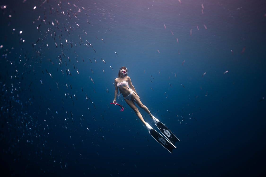 Unrecognizable woman diving in deep blue water