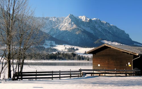 Free stock photo of frozen lake, snow capped mountains, wooden cabin