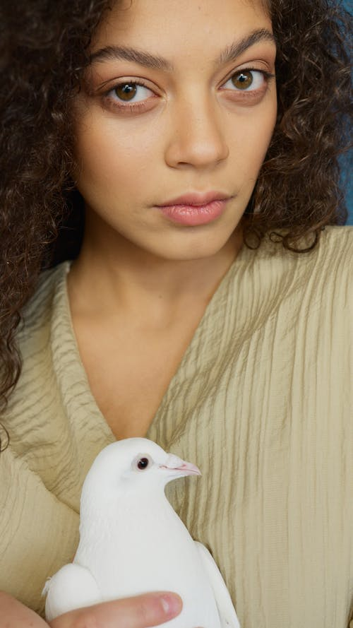 Woman in White Shirt Holding White Bird