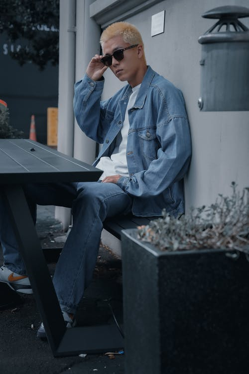 Man in Blue Denim Jacket Sitting on Black Table