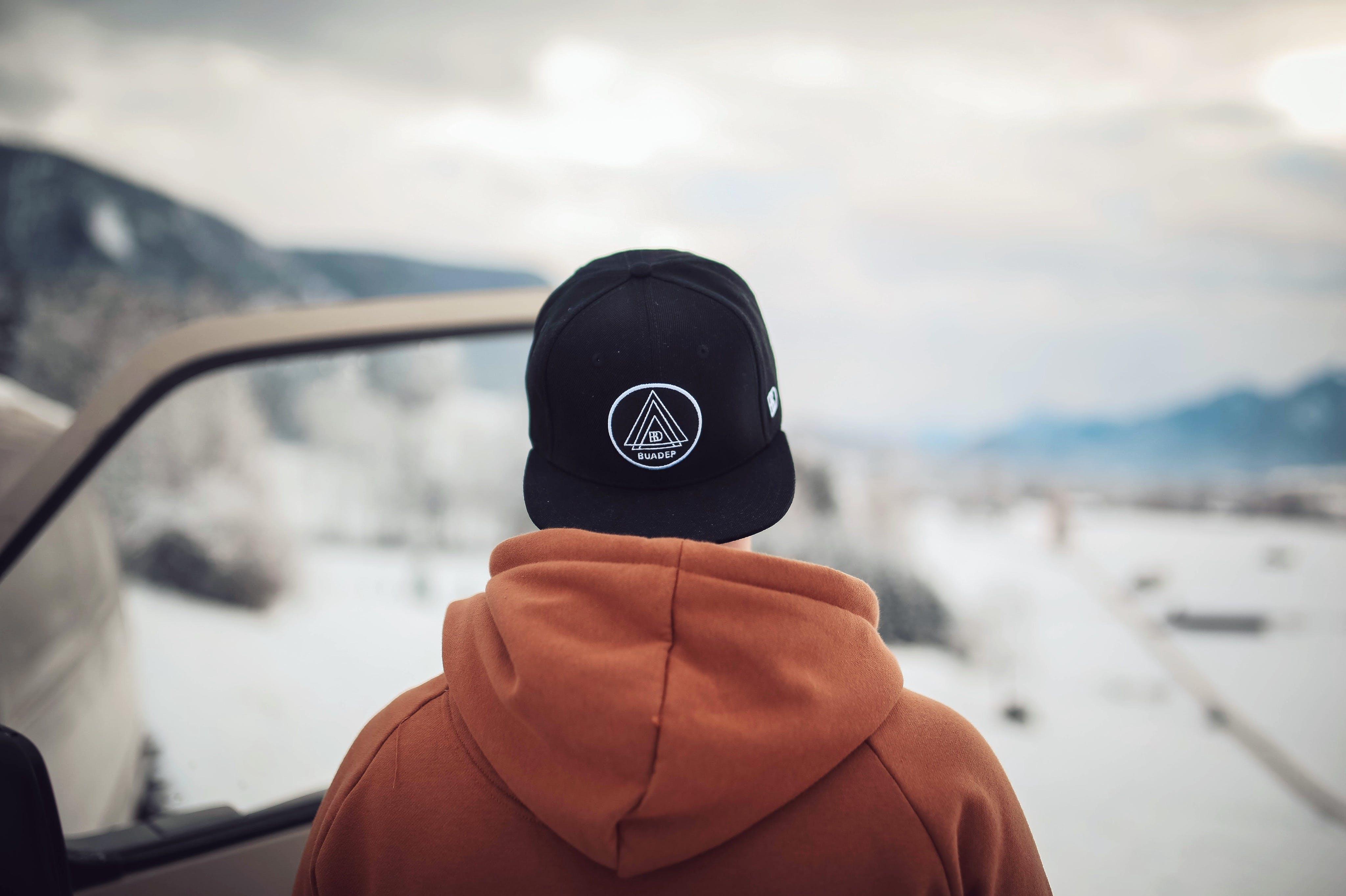 Person Wearing Black Cap and Orange Hoodie Turning His Back