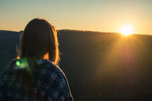 Woman Wearing Plaid Shirt Facing Sun during Golden Hour