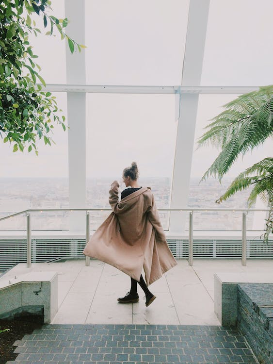 Woman Wearing A Coat While In Front of Glass Window