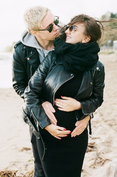 Man in Black Leather Zip Jacket Hugging Woman in Black Leather Zip Jacket and Black Pants Standing on Sand at Daytime