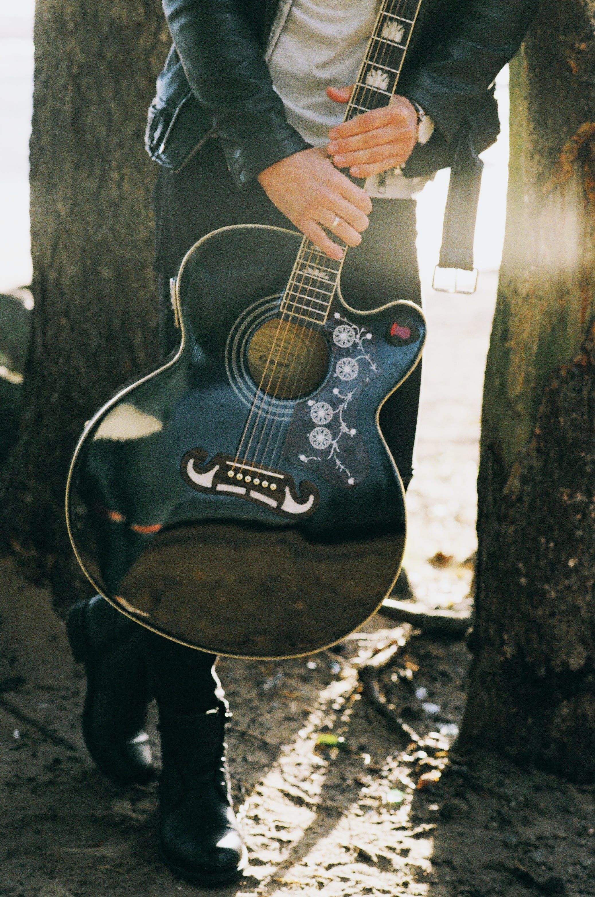 Man Holding Single Cutaway Acoustic Guitar