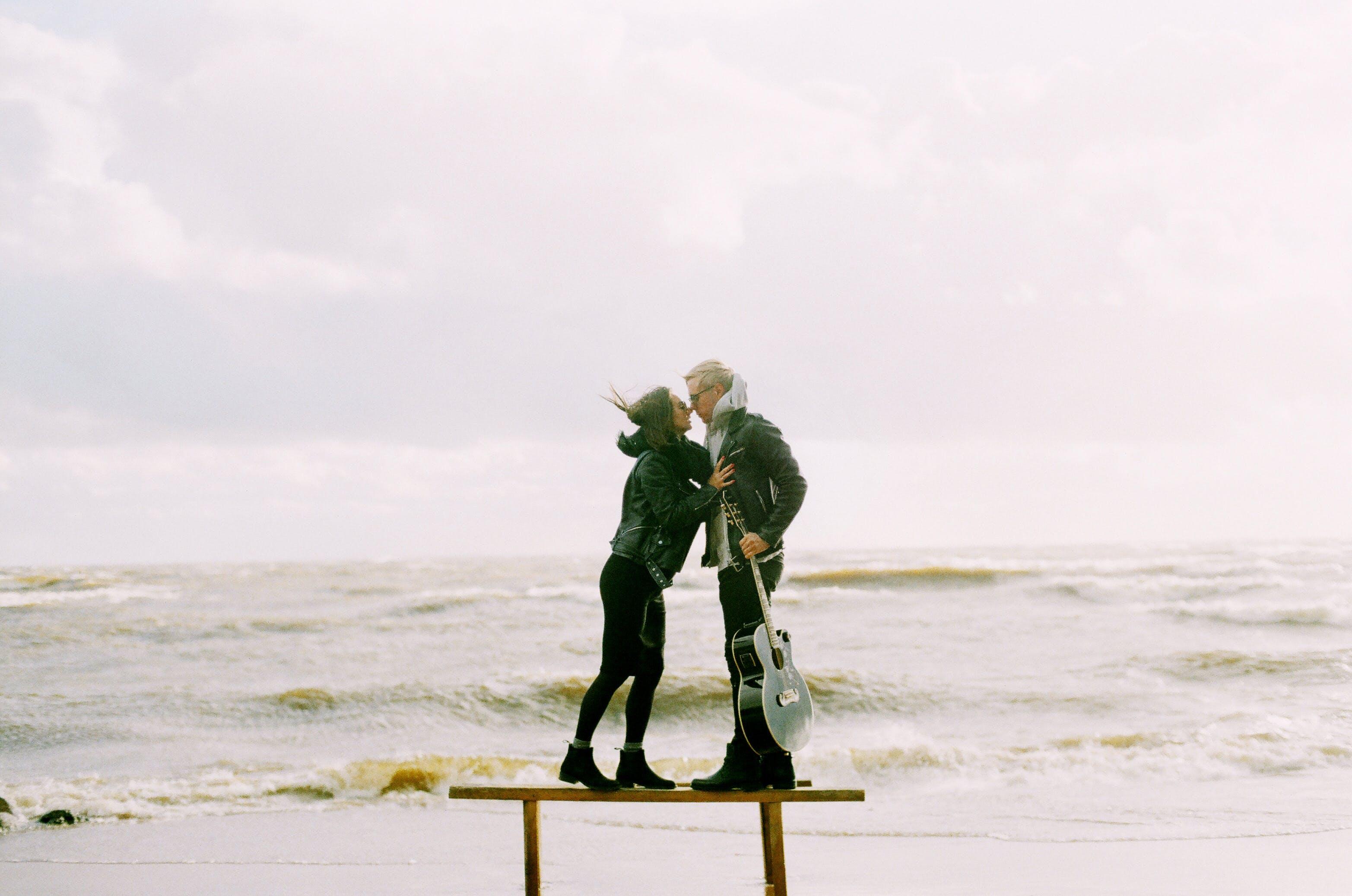 Woman Kissing Man Holding Guitar Beside Beach