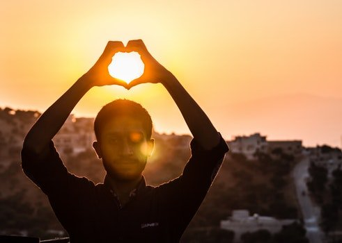 Person Making Heart Shape With His Hand During Sunset