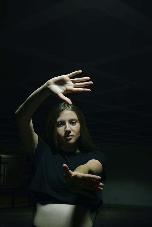 Young female with outstretched arms and shade on face looking at camera in artificial light