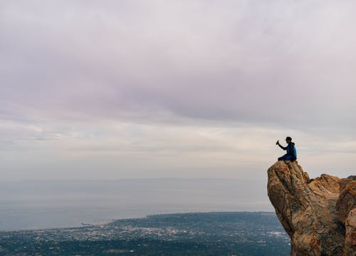Person Sitting on Mountain Edge Under Cloudy Sky