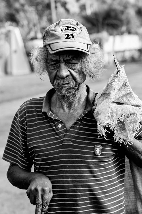 Grayscale Photography Of Man Wearing Polo Shirt And Holding Sack