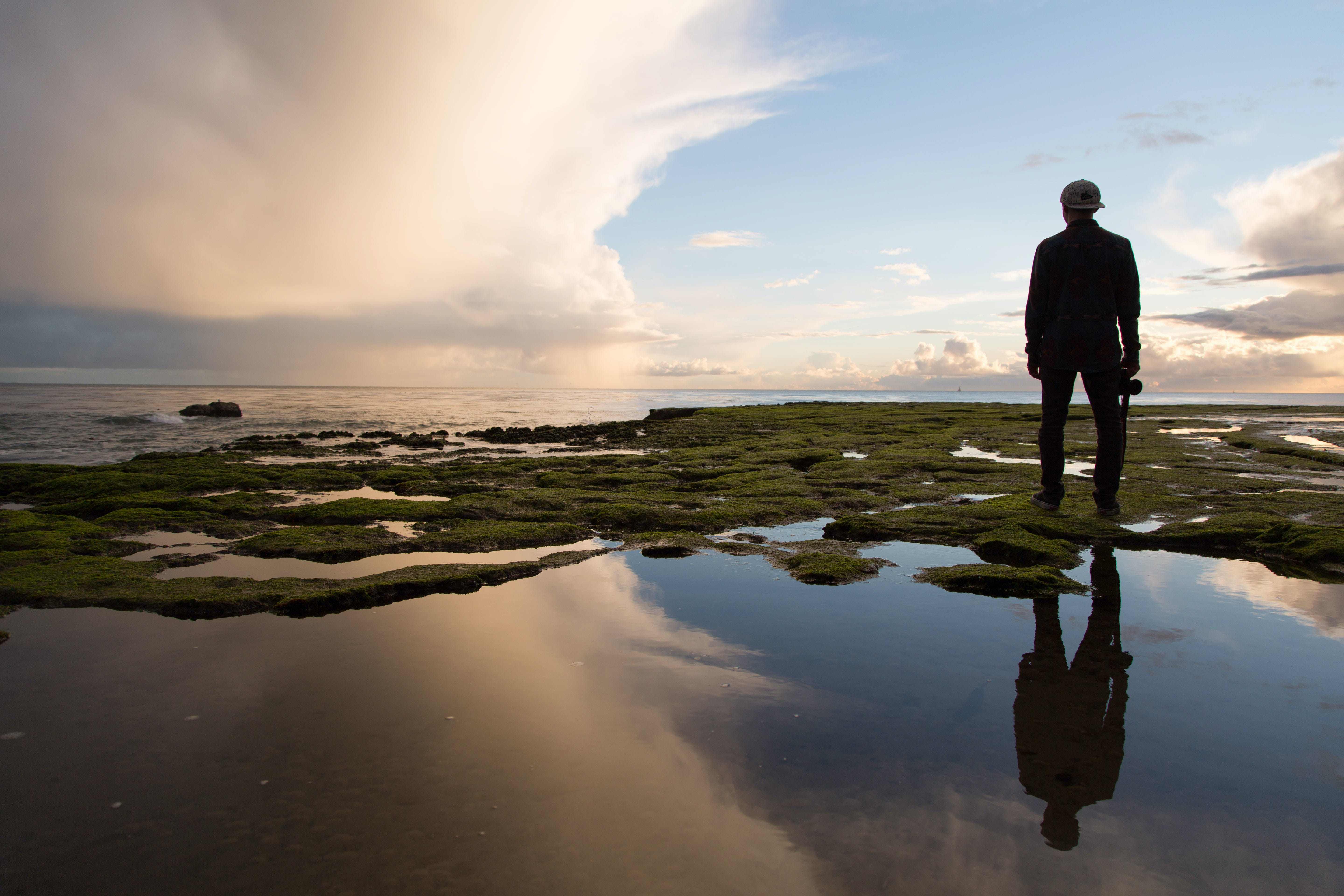 Silhouette of Man Standing on Rock Formation Near Body of Water during Golden Hour