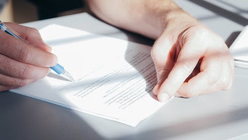 A Person Signing on a Document