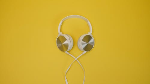 White Corded Headphones on Yellow Surface