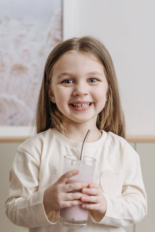 Smiling Child Holding a Glass with Straw Looking at the Camera