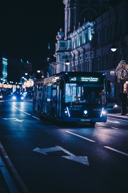 Blue Bus on Road during Night Time