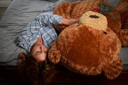 Serene woman lying on bed with big plush bear