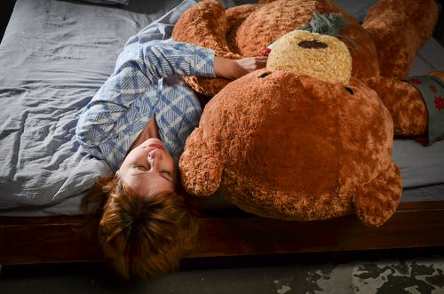 Relaxed woman lying on bed with big plush bear