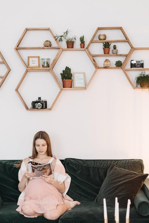 Pregnant Woman Sitting on Sofa While Reading a Magazine