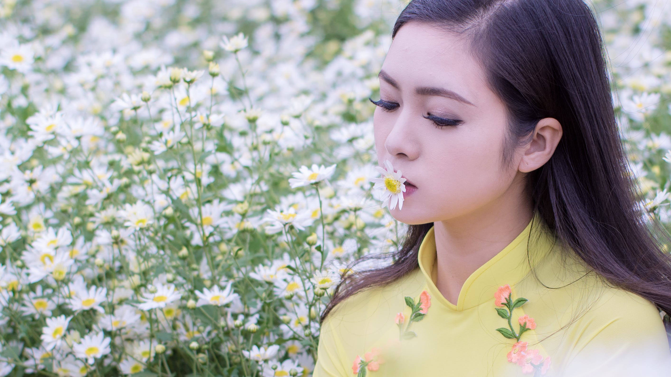 Selective Focus Photography of Woman Kissing White Petaled Flower