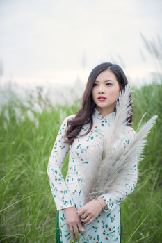 Woman in White and Green Long-sleeved Traditional Dress Standing Next-to Green Grasses