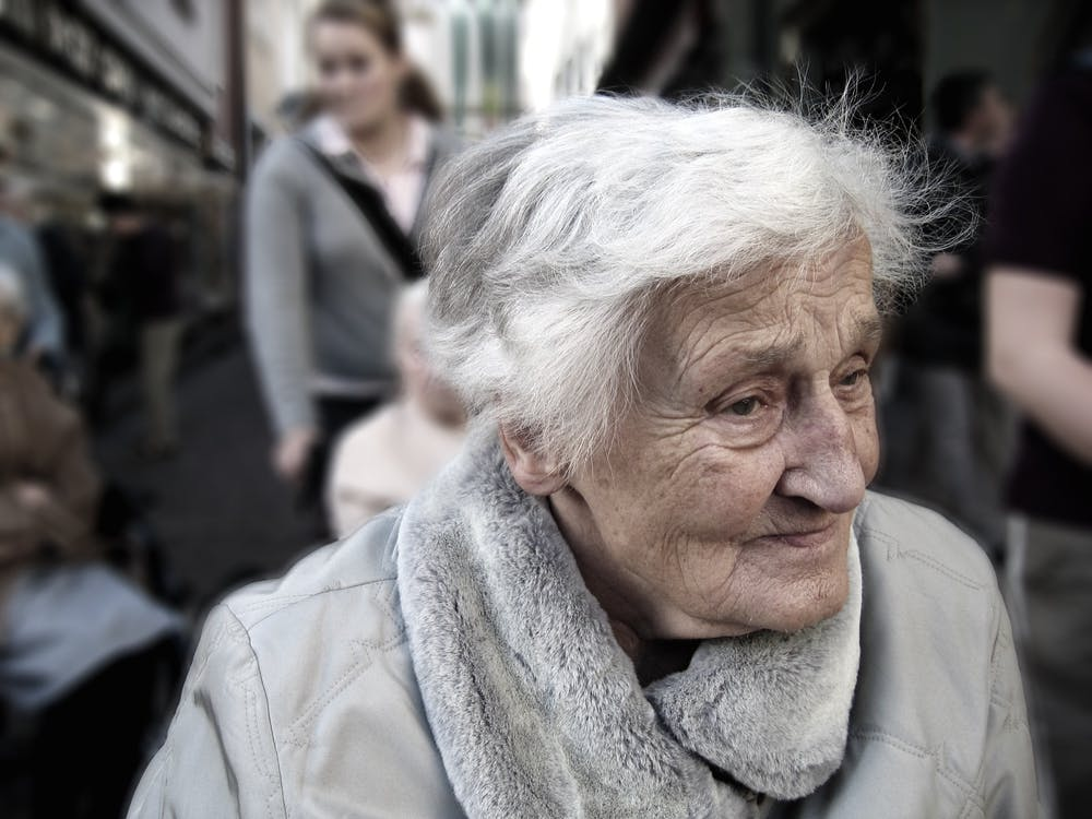 Elderly woman near group of people | Photo: Pexels