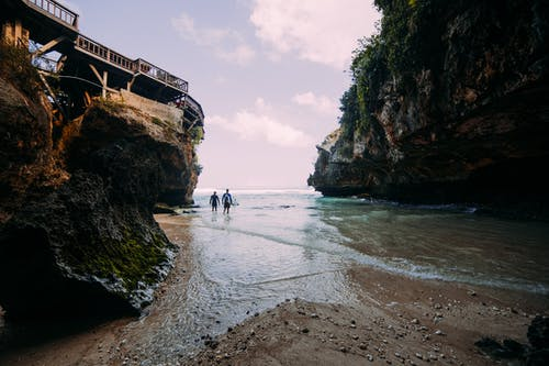 People walking on wet coast between rocks