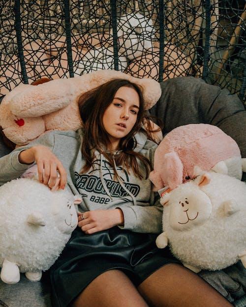 Woman in Pink Hoodie Sitting Beside White Bear Plush Toy