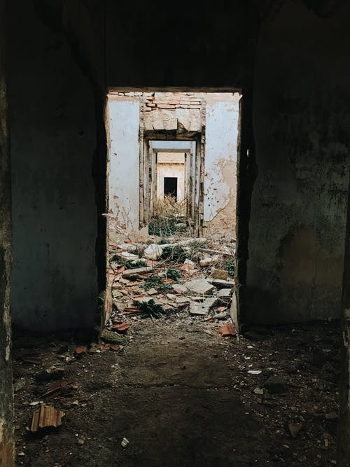 Damaged shabby uninhabited house with crumbling walls and destroyed doorways located on ground with ruins near weathered buildings in neglected district