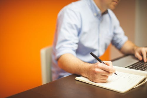 Focus Photography of Person Writing on Desk Using Laptop