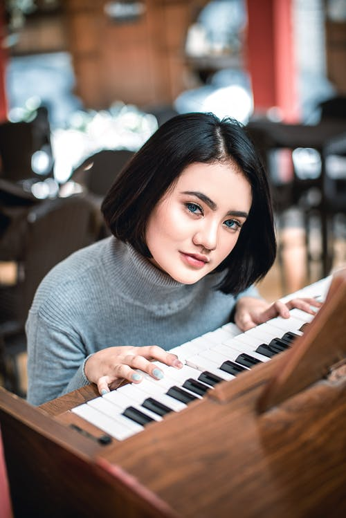 A Woman with Short Hair Playing the Piano