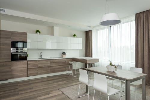 Interior of modern kitchen with wooden and white glossy cabinets and dining table with chairs in spacious apartment