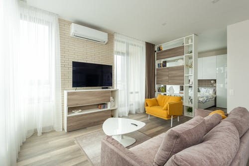 Cozy sofa and armchair placed near cabinet with TV set in contemporary living room separated from bedroom with cupboard and shelves in spacious studio apartment