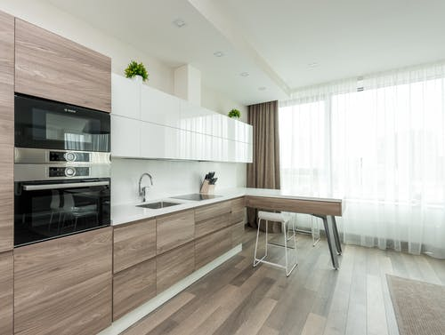 Interior of modern light kitchen with white and wooden cabinets and contemporary appliances in apartment
