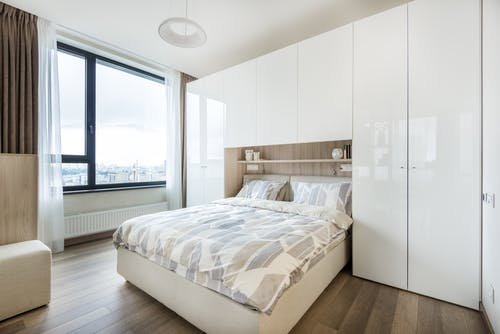 Interior of modern bedroom with white built in wall wardrobe and shelf above cozy bed with pillows and soft blanket in daylight