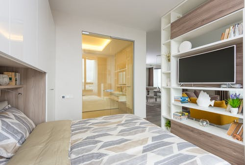 Interior of light cozy bedroom with open plan living room behind shelf partition with TV and opened glass doors to bathroom