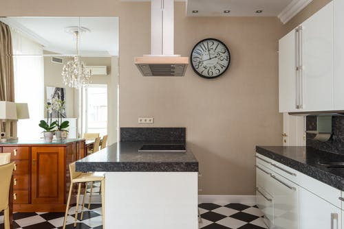 Light simple kitchen with tiled floor and island counter against dining table and mirror with cupboard