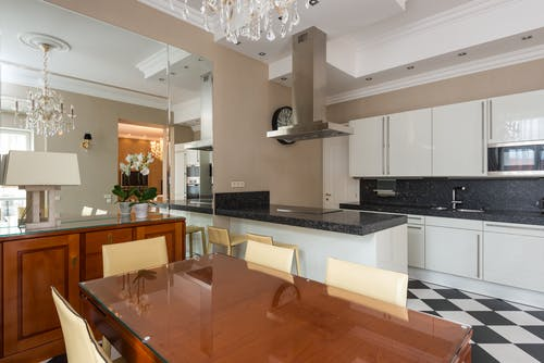 Stylish kitchen furnished with glossy cupboards and dining table with modern appliance including hood with built in stove and microwave