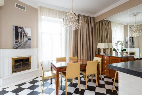 Dining table with chairs placed near window covered with curtains in kitchen with classic chandelier in apartment